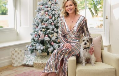Liz sits in a Christmas scene with a dog