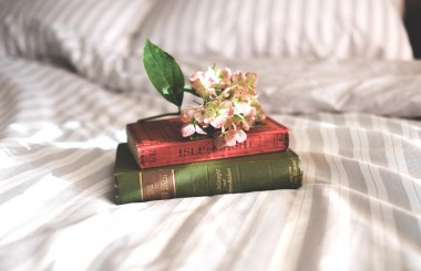 pile of books on bed